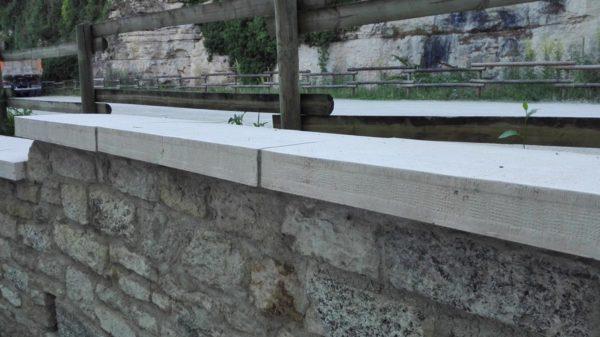 Dessus de muret, couvertine 1 m, aspect bombé, bouchardé et ciselé, en pierre reconstituée . Visible à Bèze, 21310, Bourgogne, vers le parking du site des grottes (la source de la Bèze).