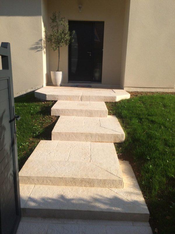 Construction d'un escalier extérieur en blocs marches pleins, finition ciselée-bouchardée. Fabrication sur-mesure.