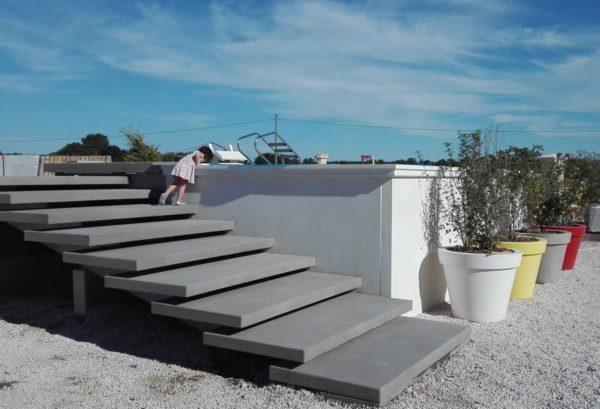 Une piscine hors sol, dimensions 3 m x 6 m, composée d'éléments préfabriqués en béton lisse ne nécessitant pas d'enduit. Produits complémentaires: un grand escalier béton à crémaillères, une plage de piscine, des corniches et des margelles.