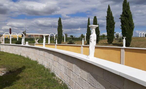 Mur de clôture revêtu des plaquettes de parement et des couvertines plates en pierre reconstituée