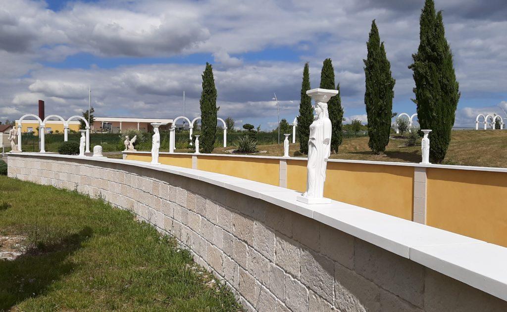 Mur de clôture revêtu des plaquettes de parement et des couvertines plates en pierre reconstituée.