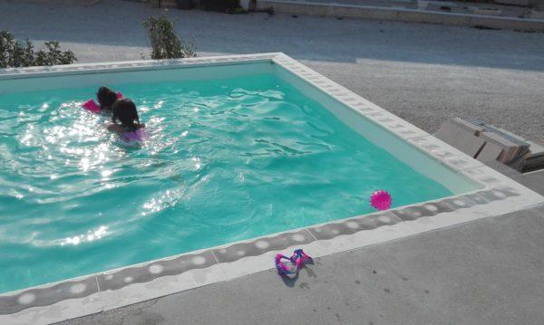 Une piscine préfabriquée en béton, modèle hors sol, aménagée avec une plage de piscine, des corniches et des margelles.