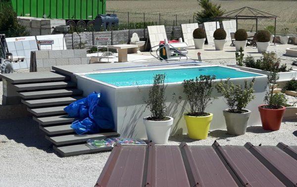 Une piscine en panneaux préfabriqués en béton lisse, hors sol ou semi-enterrée; avec un escalier préfabriqué en ciment gris.