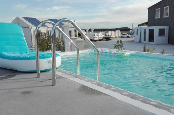 Une piscine hors sol préfabriquée en béton lisse, avec une plage de piscine et des margelles contemporaines, modèle 'jeux de lumière'.
