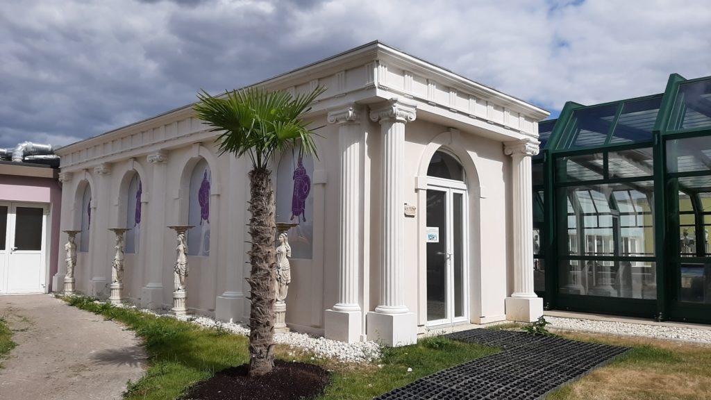Locale technique style temple grec décoré avec des colonnes cannelées classique en pierre reconstituée.
