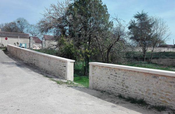 Couvre-murs (couvertines) en pierre reconstituée, aspect bouchardé-ciselé, visibles à Arcelot, 21310, en face du Château d'Arcelot (Bourgogne).