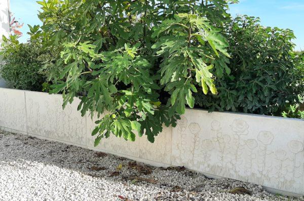 Muret de clôture en béton moulé / pierre reconstituée avec une face décorative, motif 'roses', version muret en L.