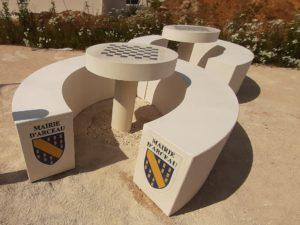 Table rond béton et bancs béton arrondis, personnalisé avec le blason de commune.